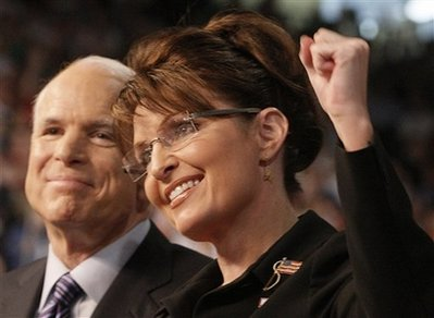 Sarah Palin in seen pumping her fist in the air, with John McCain smiling in the background