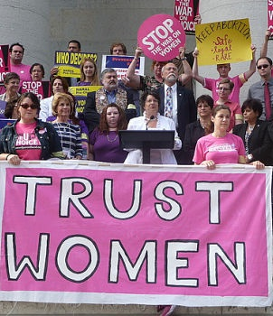 """ID: Image of activists holding a pink banner that says """"trust women."""" This morning, John Boehner vowed to overturn the provision in the PPACA that would require faith-affiliated institutions to cover employees' contraception."""
