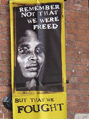 "ID: image of a poster that features a Black woman's face in black and white and the words ""Remember not that we were freed, but that we fought."" ""Slave Rape"" and the Story of Sukie"