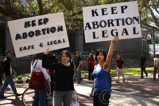 "ID: two people holding up signs that say ""keep abortion safe and legal"" and ""keep abortion legal"" -- as we win on the contraception front, we can't forget abortion rights."