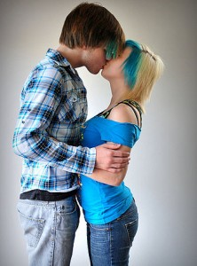 ID: Image of two young adults embracing and kissing. One wears a plaid blue button down and the other a blue off-the-shoulder- shirt, both wear jeans and have a blue streak in their hair. title: sex education as a human right