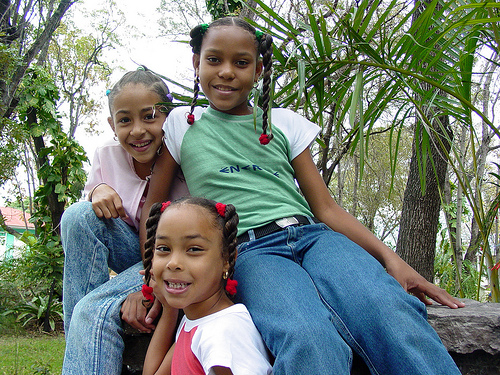 ID: image of three young people with their hair in braids, smiling and looking at the camera. the future of feminism is now!