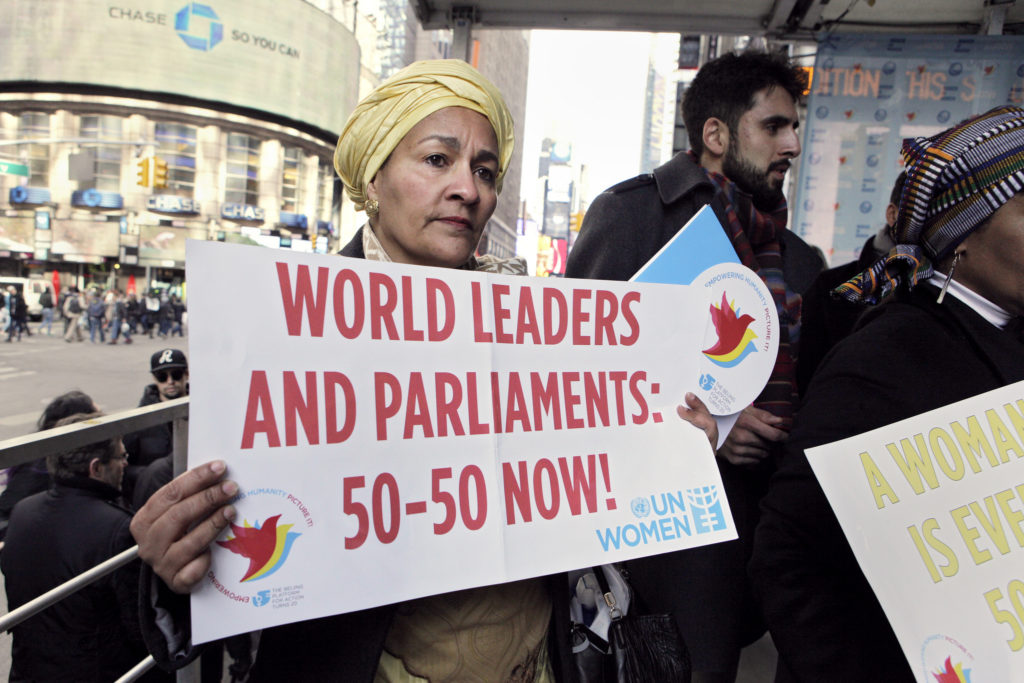 a woman holds a sign reading WORLD LEADERS AND PARLIAMENTS: 50-50 NOW!