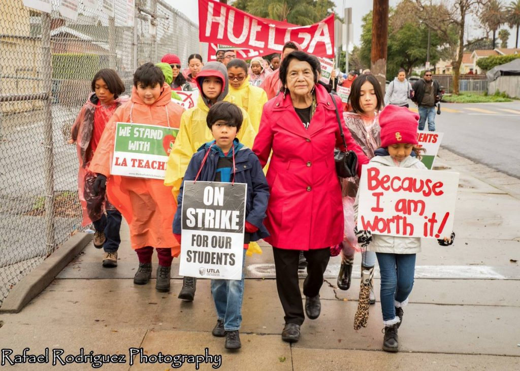 dolores huerta, wearing red, joins teachers and students in a rainy Los Angeles schoolyard.