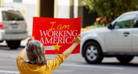 a woman holds a sign that reads I AM WORKING AMERICA