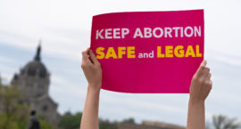 "A person holds up a protest sign that reads, ""Keep Abortion Safe and Legal."""