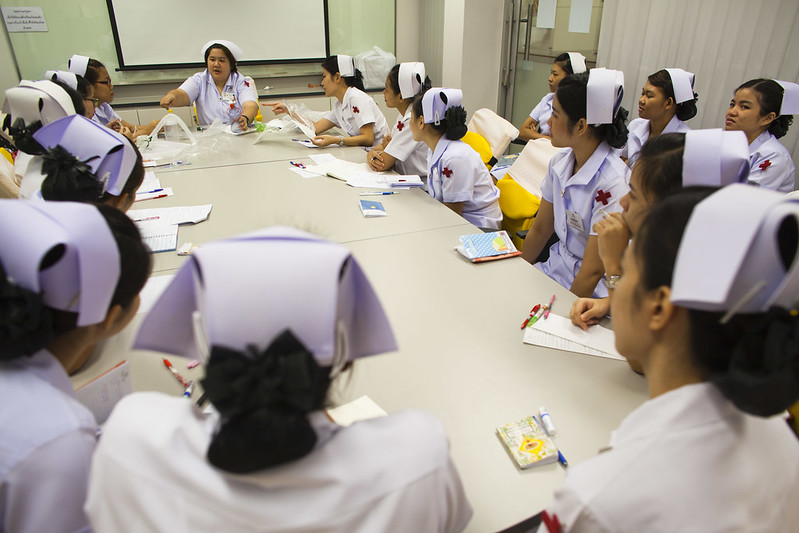 Nurses sit around a table during a meeting.