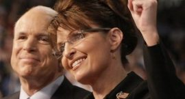Sarah Palin raises her fist while smiling. John McCain is seen smiling in the background.