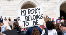 """protester holds sign reading, """"My body belongs to me"""""""