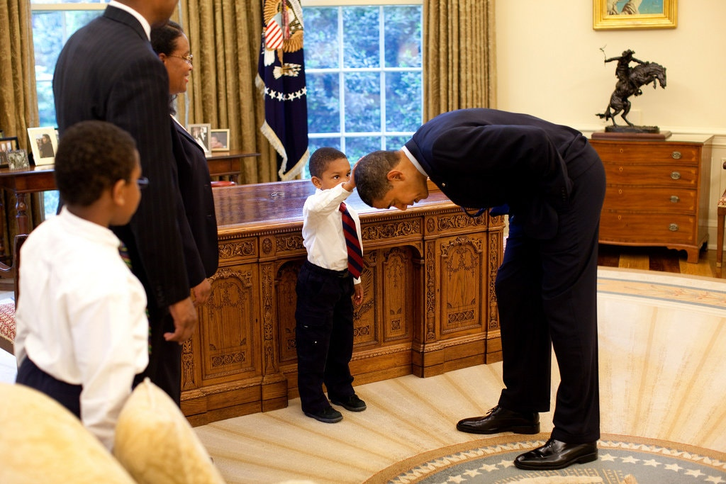 President Obama bends over as 5-year-old Jacob Philadelphia touches his hair.