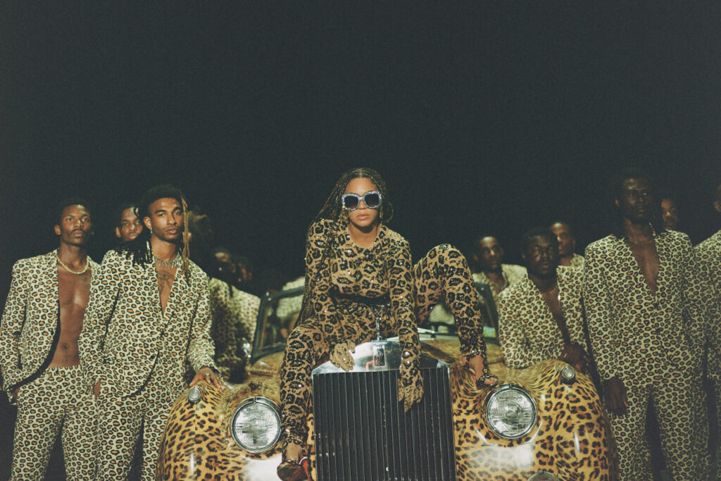 ID: Still from Beyonce's Black is King , showing beyonce dressed in leopard print seated on the hood of a leopard print car surrounded by black men in leopard print suits
