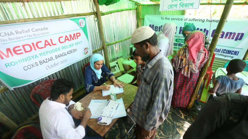 """I Have To Go Back"": Doctor Spearheads Fight Against COVID in Rohingya Refugee Camp. ID: image of Dr. Fozia Alvi sitting at a table under a sign that says ""Medical camp: rohingya refugee relief 2017 cox's bazar, bangladesh."" she is filling out a form. a group of people stand around in front of the table."