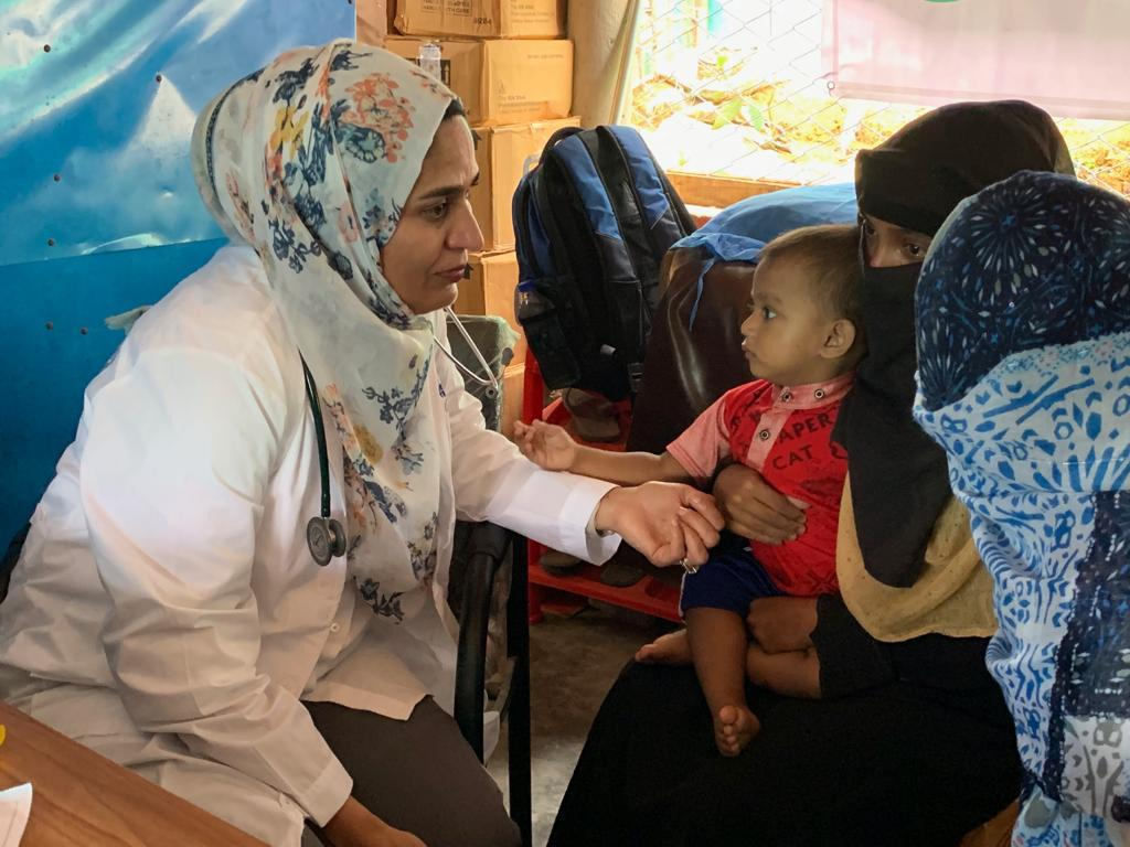"""I Have To Go Back"": Doctor Spearheads Fight Against COVID in Rohingya Refugee Camp. ID: image of Dr. Fozia Alvi wearing a white coat, stethoscope, and headscarf sitting at a desk with another woman wearing a niqab, holding a child."
