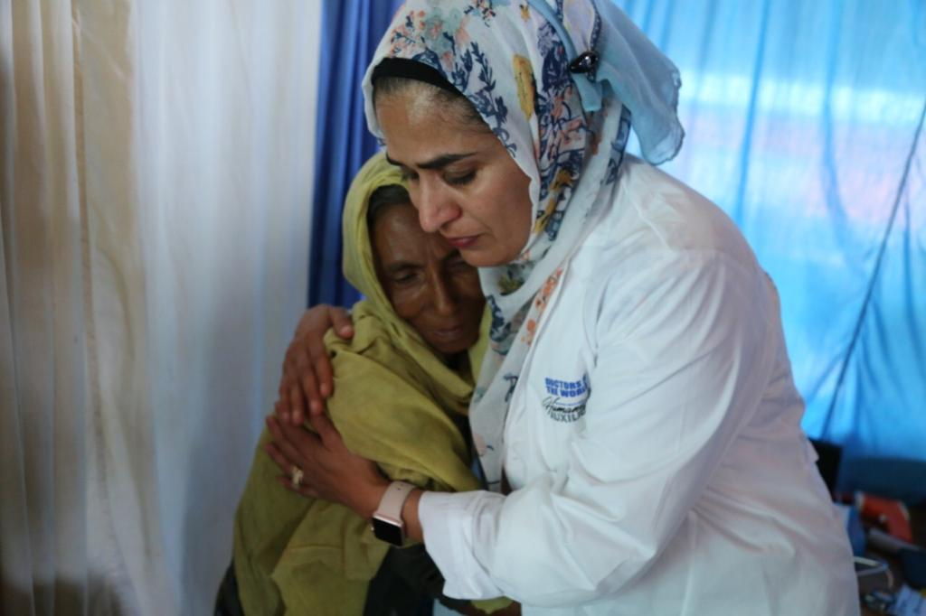"""I Have To Go Back"": Doctor Spearheads Fight Against COVID in Rohingya Refugee Camp. ID: image of Dr. Fozia Alvi, embracing an older woman"