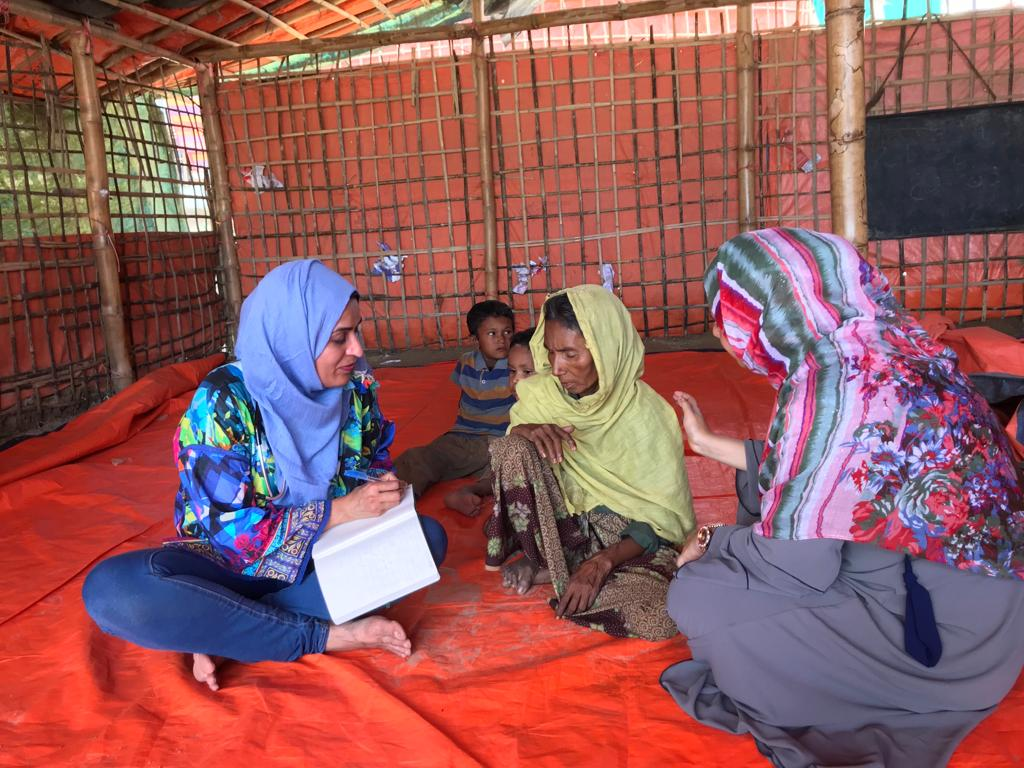 """I Have To Go Back"": Doctor Spearheads Fight Against COVID in Rohingya Refugee Camp. ID: image of Dr. Fozia Alvi seated on a red carpet with two other women, writing in a notebook. two children sit in the background"