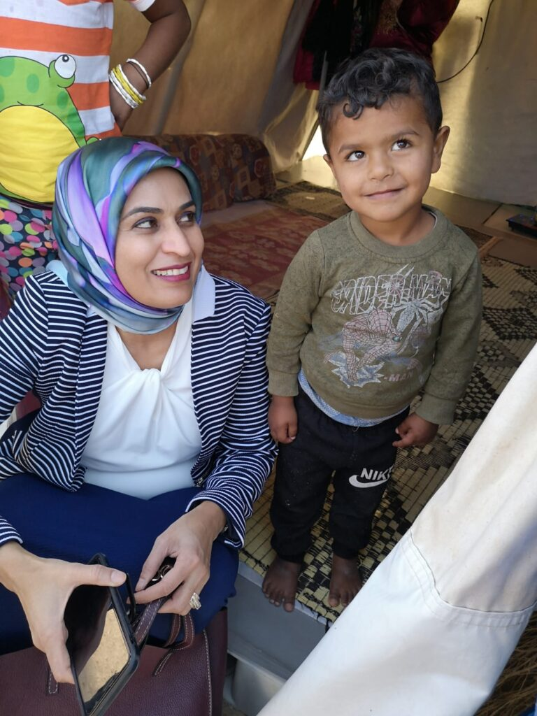 """I Have To Go Back"": Doctor Spearheads Fight Against COVID in Rohingya Refugee Camp. ID: image of Dr. Fozia Alvi sitting and smiling, looking at a small child, also smiling and looking up."