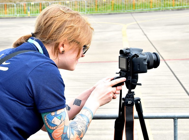 ID: image of a person wearing a blue shirt with red hair in a ponytail operating a digital camera on a tripod. women media