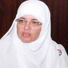 ID: a heaadshot of Azza El Garf. She wears glasses and a white headscarf.