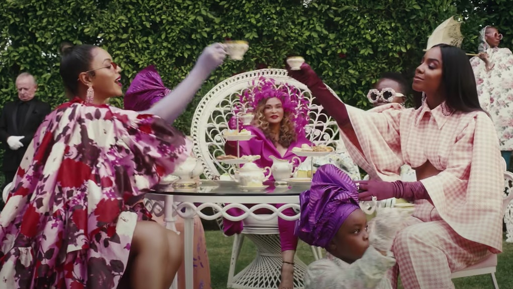 ID: Still from Beyonce's Black is King , depicting several black women and one young girl dressed in a variety of pink outfits at a tea party.
