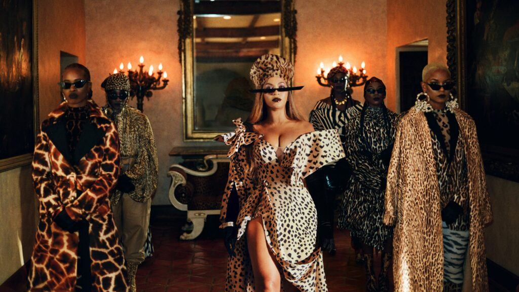 ID: Still from Beyonce's Black is King , depicting beyoncé and several others standing in a low-lit room with candelabras and a  mirror behind them, facing the camera, all dressed in a variety of leopard print outfits.