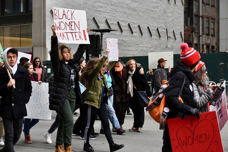"""ID: image of a group of people at a protest. In the foreground, a young person holds up a sign that reads """"Black women matter!"""""""