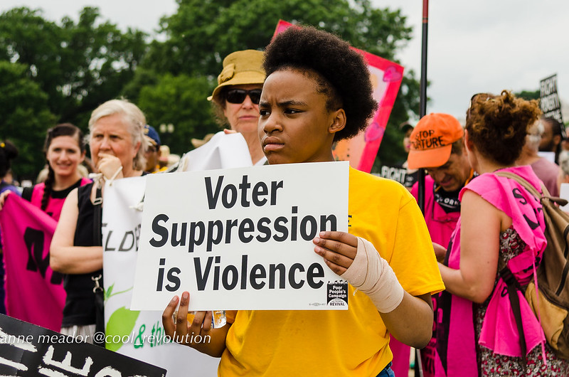 """ID: Image of a young dark skinned person with short hair in a yellow t shirt at a protest holding a sign that reads """"voter suppression is violence"""""""