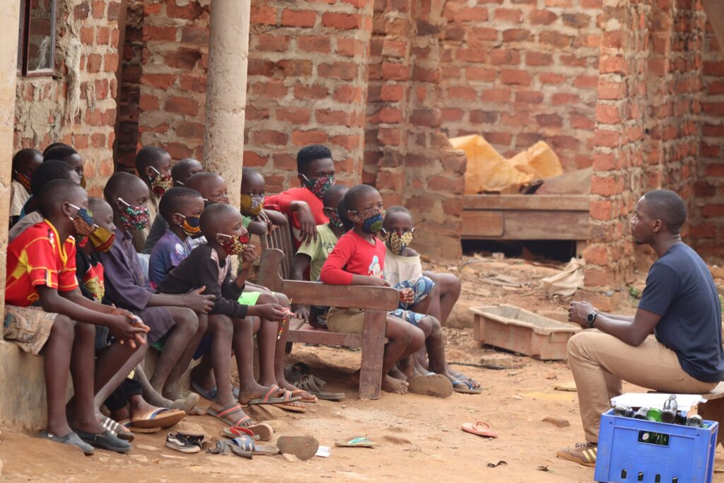 ID: an adult sits across from a group of mask-wearing children seated on benches. COVID-19 is putting global education equity for girls at risk.