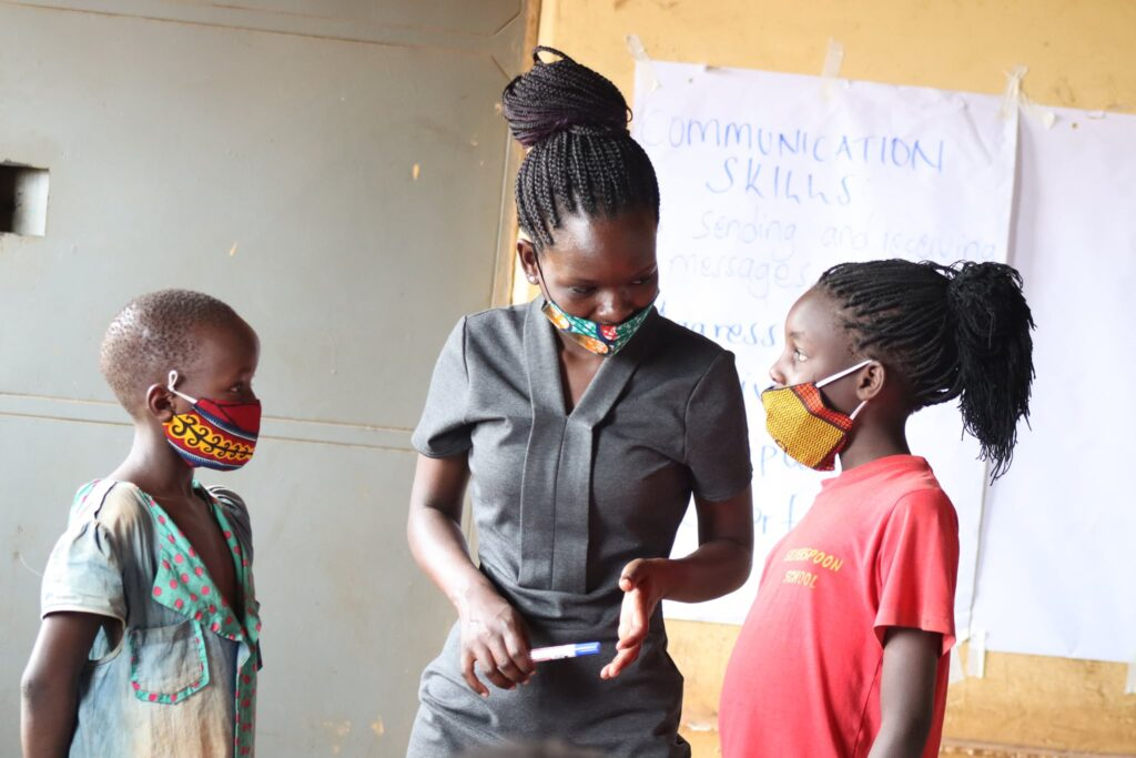 ID: Image of an adult talking to two children, all wearing masks. COVID-19 is putting global education equity for girls at risk.