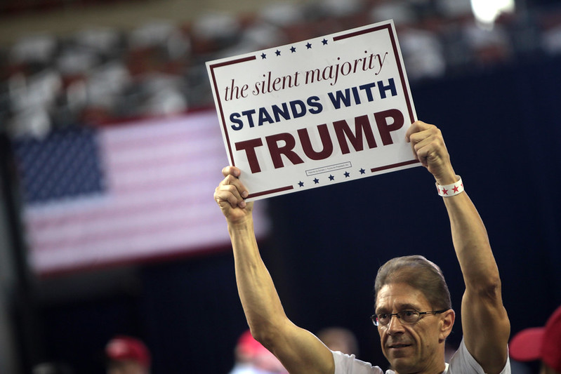 "What Donald Trump Understands about American Men Image description: a photo of a person's head and shoulders, they are at a rally holding a sign above their head that reads ""the silent majority stands with trump"""