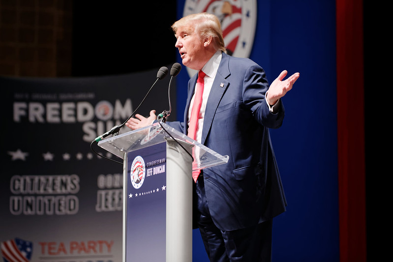 What Donald Trump Understands about American Men Image description: a photo of Donald Trump standing at a podium. He is speaking and gesturing with his hands.