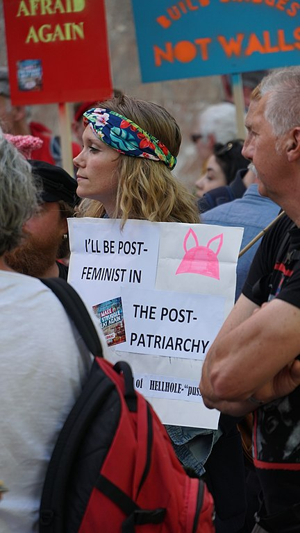 "What Donald Trump Understands about American Men Image description: a photo of a person with long curly hair wearing a colorful headband and holding a sign that reads ""I'll be post-feminist in the post-patriarchy."""