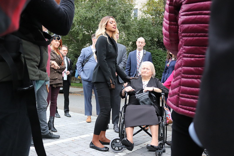 Elliot Page: What the Media Got Right  Image Description: a picture of a group of people standing around two women, one of whom is seated in a wheelchair.