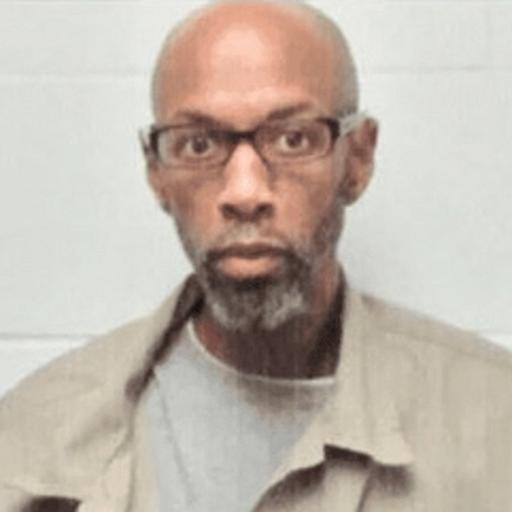 Image description: a mugshot of a Black man with a beard wearing glasses and a khaki shirt