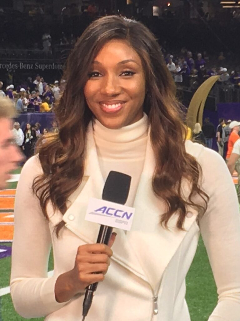 ESPN commentator Maria Taylor, whose colleague Rachel Nichols perpetuated racist sexism against in a statement, standing in front of a football field with microphone.