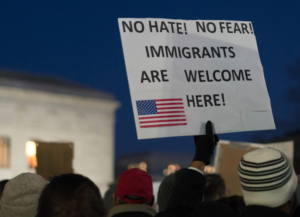 """A sign is held above the heads of protestors reading """"No hate! No fear! Immigrants are welcome here!"""" with an American flag below. VIISTA, working to meet the need for migrant legal representation, has a promising future in the fight for migrant rights."""