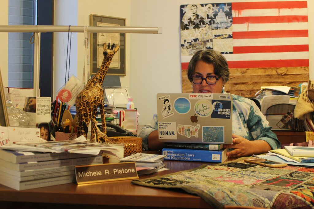 Professor Michele Pistone sitting at her desk on her laptop adorned with #RefugeesWelcome stickers. Her program VIISTA is entirely online and asynchronous, meaning that students can tune in virtually from anywhere in the country.