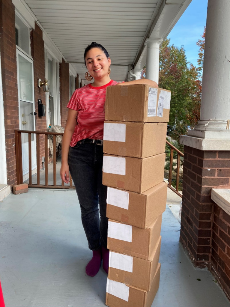 Jo Morganelli standing next to a stack of boxes with supplies for the peer-to-peer EC network she runs in Maryland.  student-emergency-contraception-vending-machines-plan-b